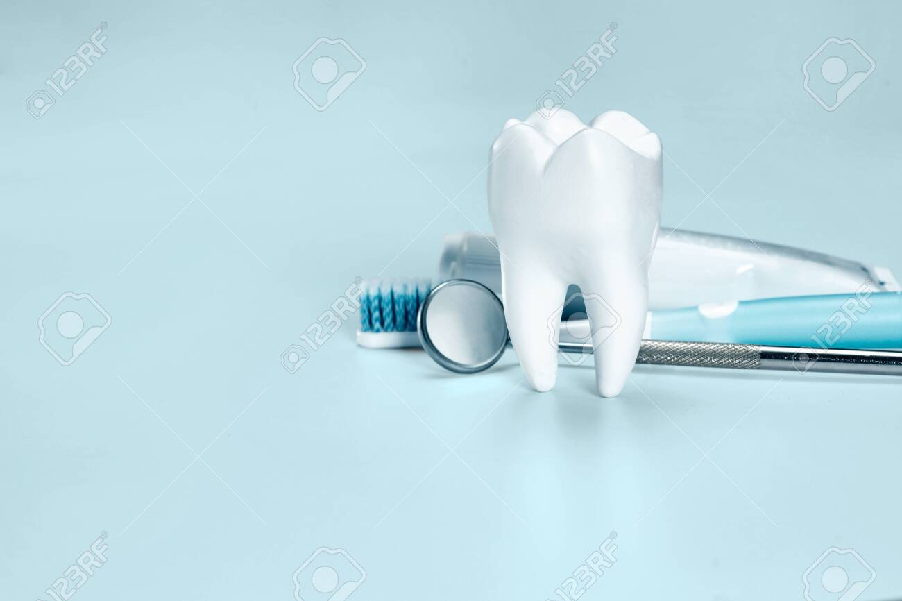 White big healthy tooth, toothbrush and toothpaste for dental care. On light blue dental background. - 120734515