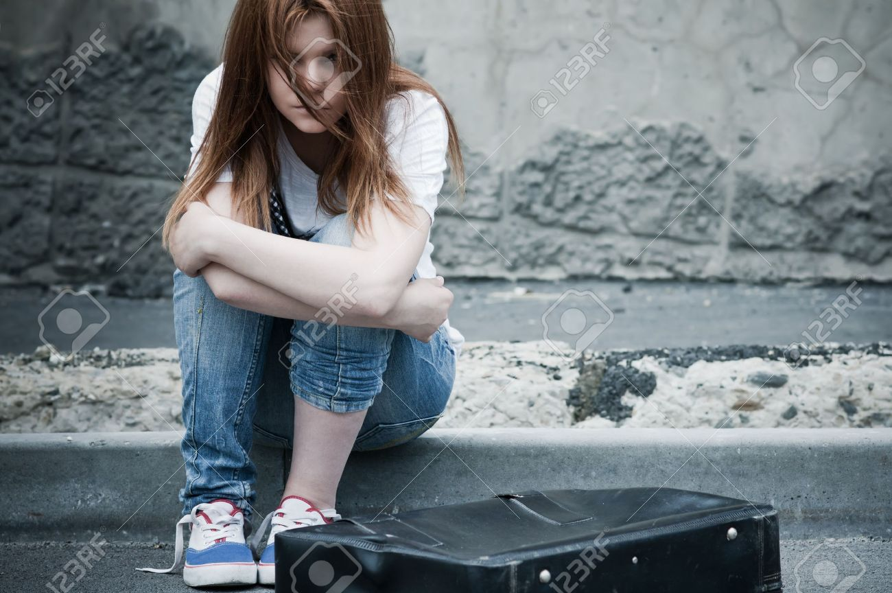 Beautiful young sad girl sitting on asphalt. Photo in cold faded tones Stock Photo - 10084993