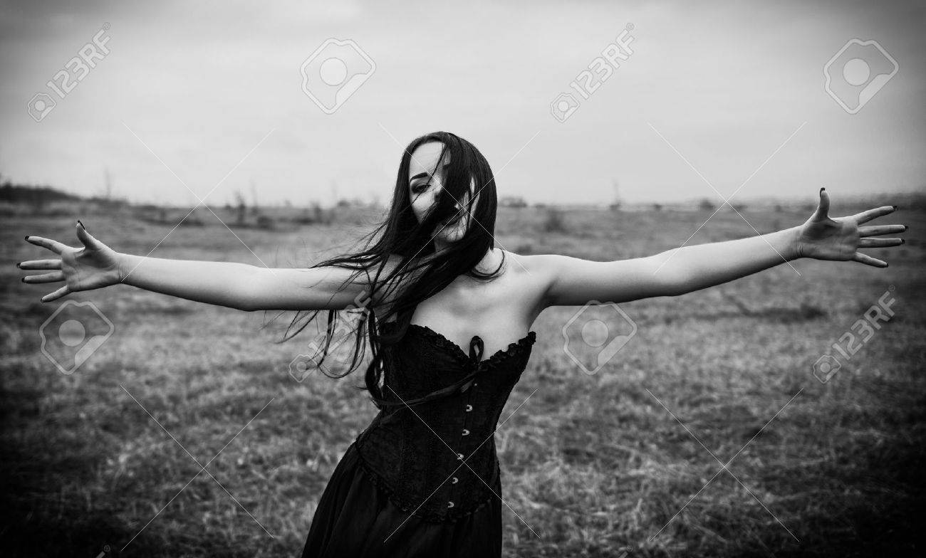 Crying sad goth girl in the autumnal field black and white photo stock photo