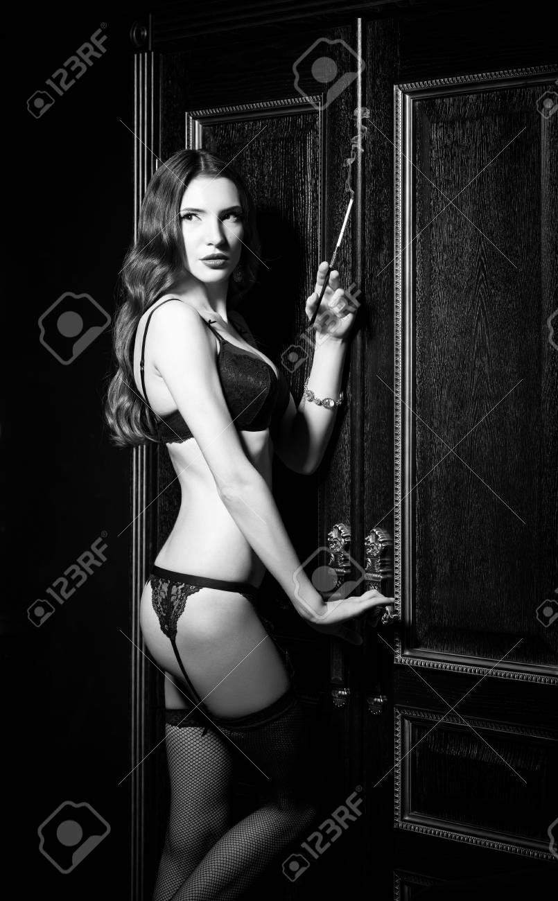 moitié prix acheter pas cher vente chaude Style de film noir: sexy jeune femme en sous-vêtements debout à la porte et  fumer cigarette