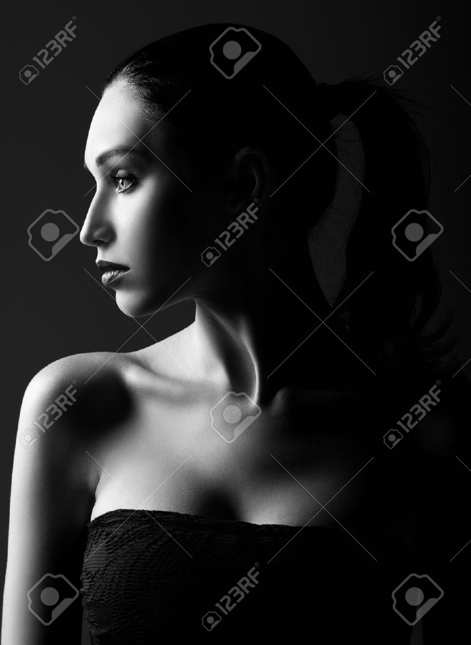 Stock photo studio shot dramatic portrait of a beautiful young woman profile view black and white