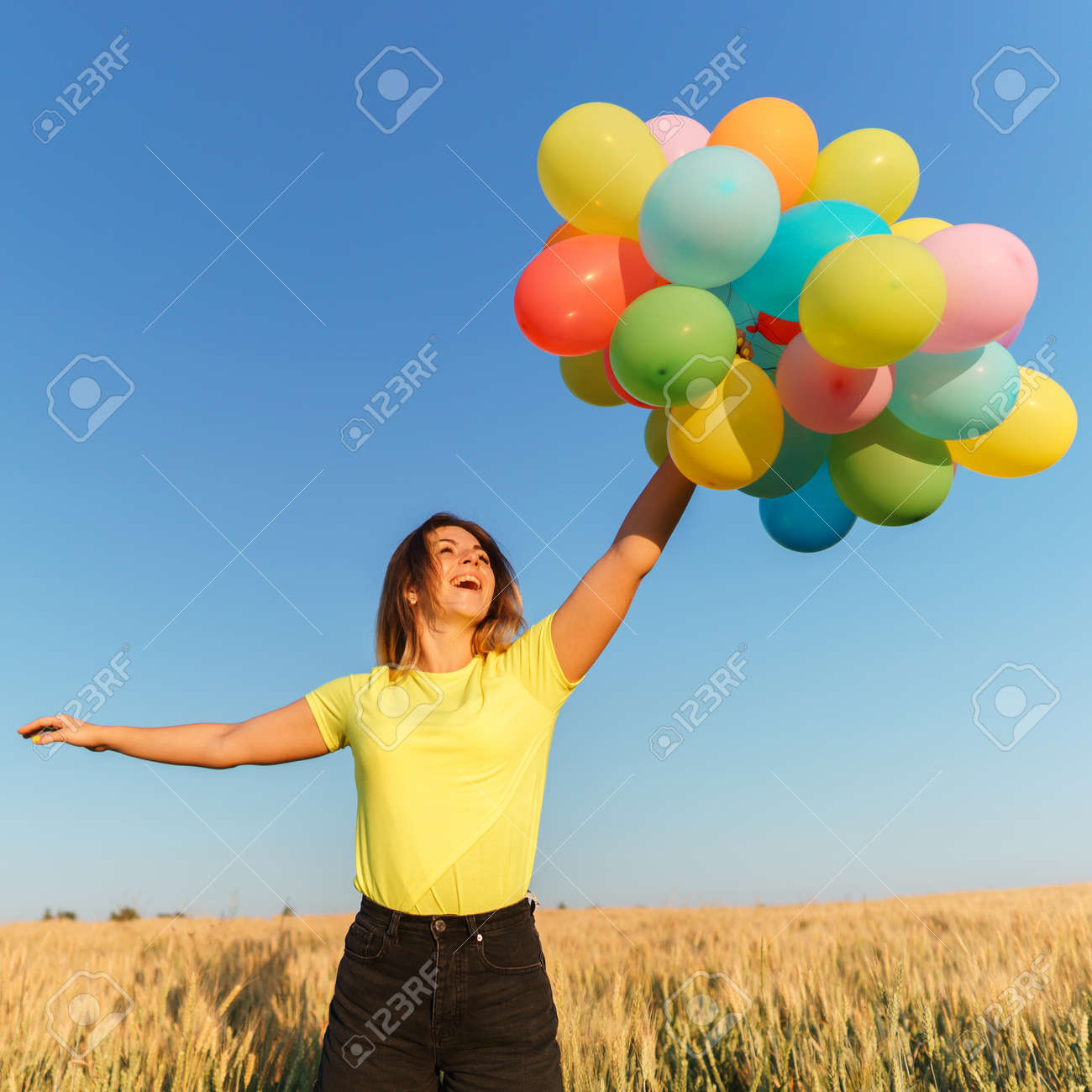 Young girl with colorful balloons in sunset meadow - 126427549