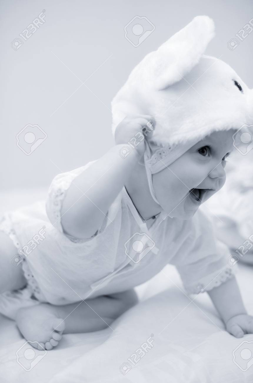 Shouting child on the bed trying to pull off funny cap from his head, black and white Stock Photo - 6087301