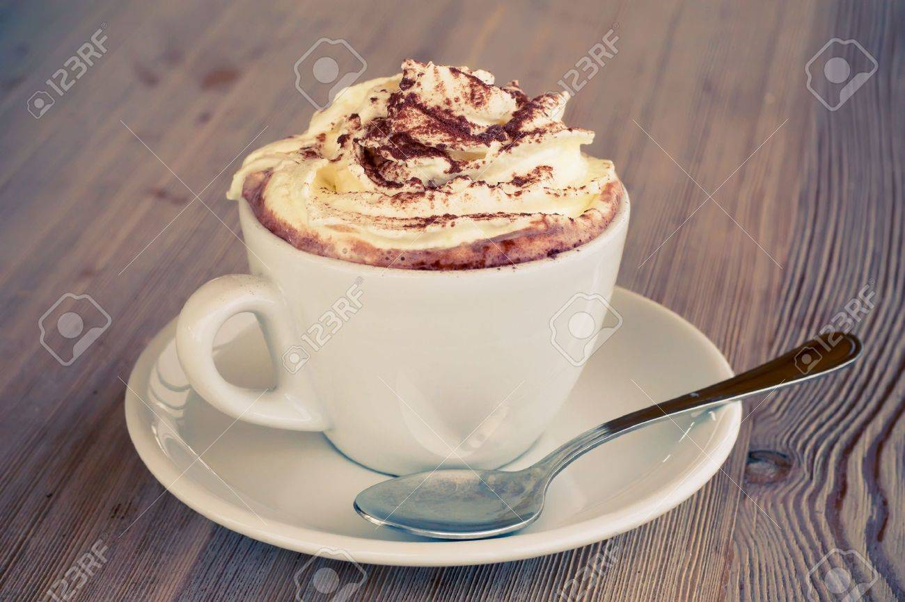 A cup of hot chocolate with cream on a wooden textured table Stock Photo - 6197843