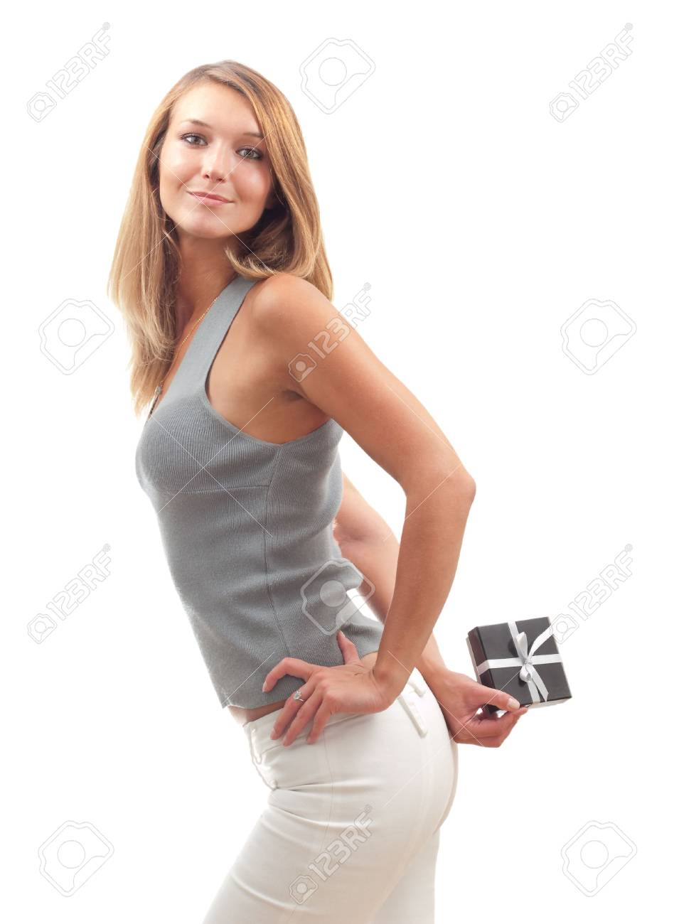 Beautiful young woman hiding a gift behind her back Stock Photo - 6784597