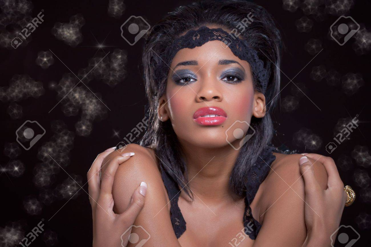 Young beautiful black woman, on black with party lights Stock Photo - 7941464
