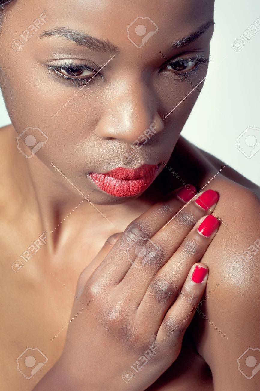 Closeup shot of a young woman with natural eye makeup, red lips and matching manicure Stock Photo - 8849259