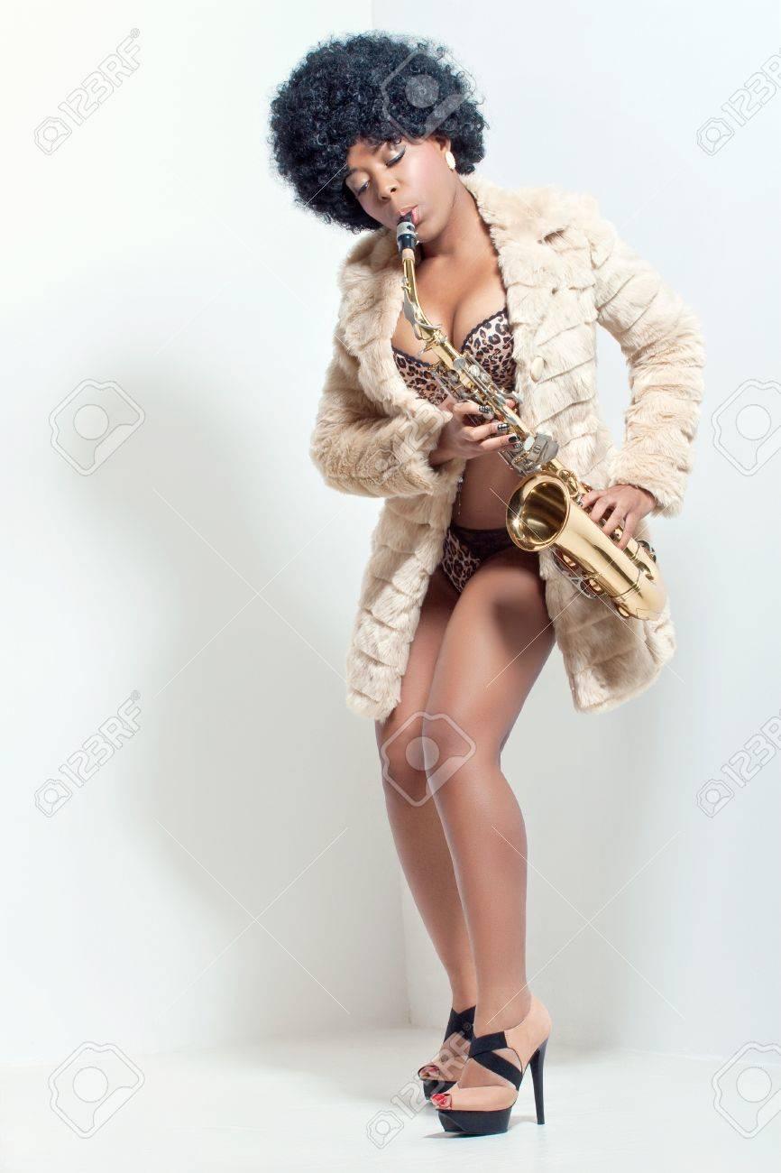 Beautiful energetic woman playing the saxophone, retro style studio portrait Stock Photo - 8853526