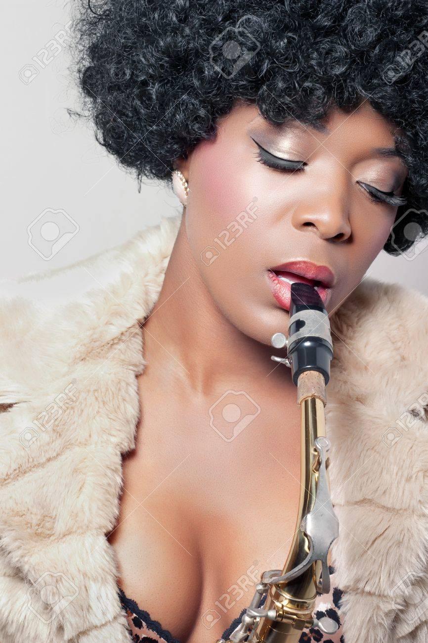 Young beautiful african woman playing a saxophone, closeup shot Stock Photo - 10669115