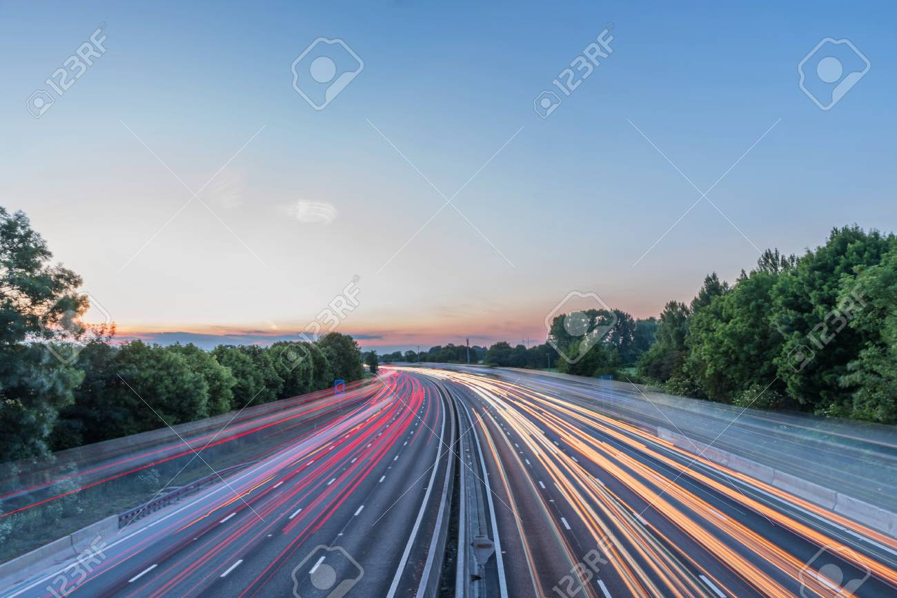 Sunset view heavy traffic moving at speed on UK motorway in England - 103963592