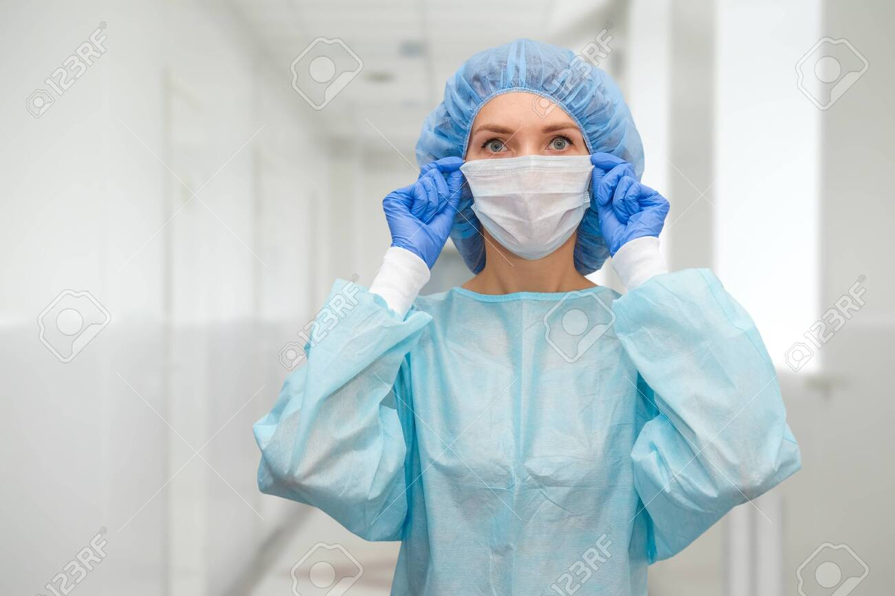 Portrait of doctor in scrubs. A female doctor in a protective cap and face mask in safety measures against the coronavirus. - 148926402