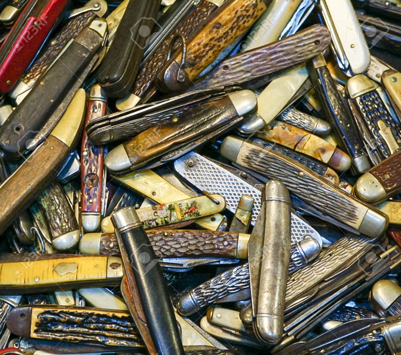 An up close view of a collection of old vintage pocket knives