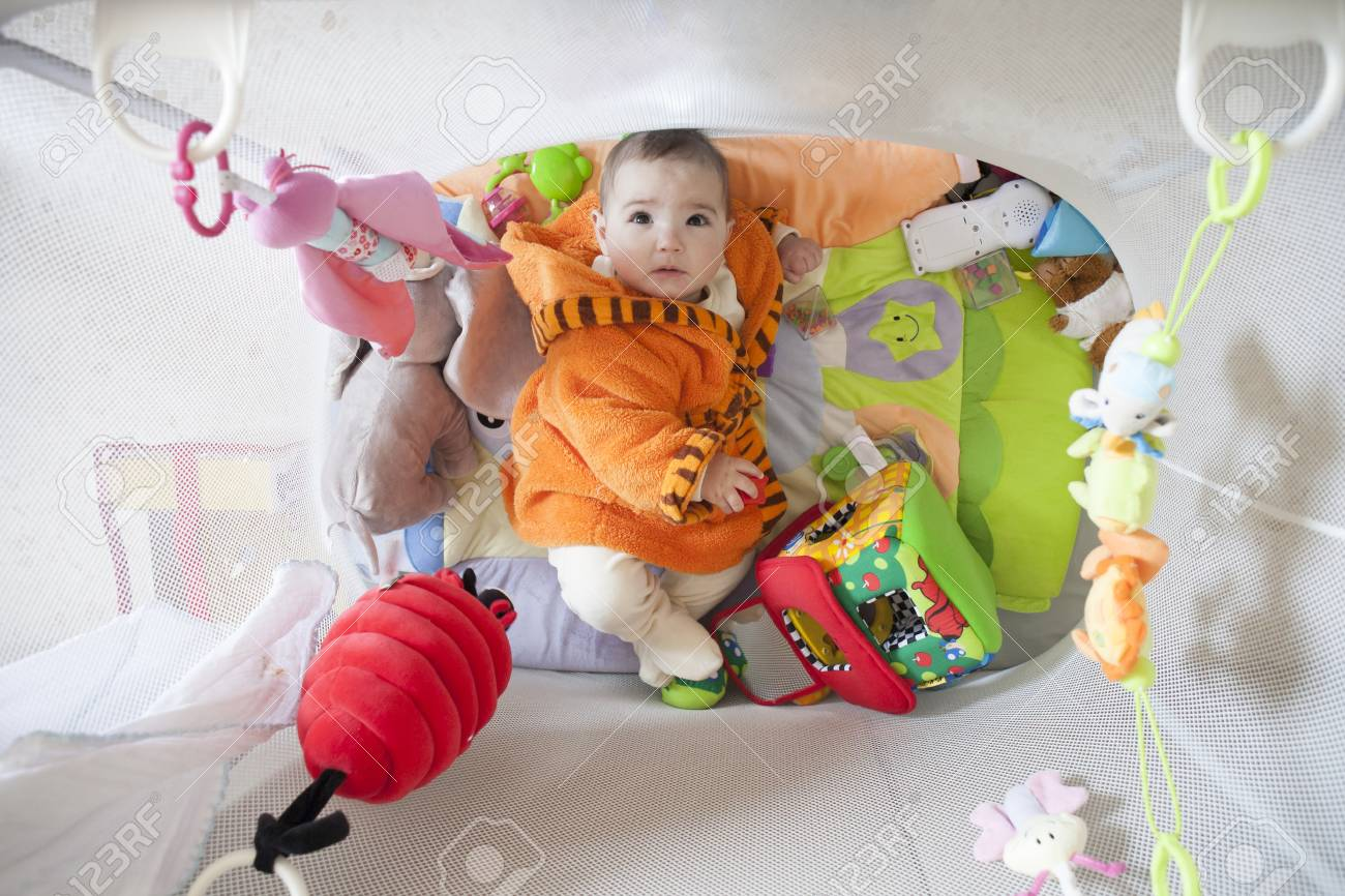 Cute Baby Girl At Playpen Full Of Soft Toys 8 Months Old Stock