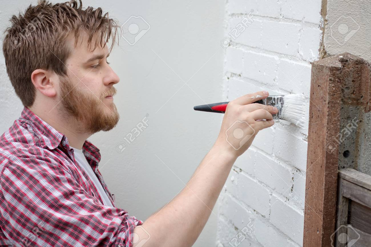 Man painting house wall with brush  DIY Home Improvement