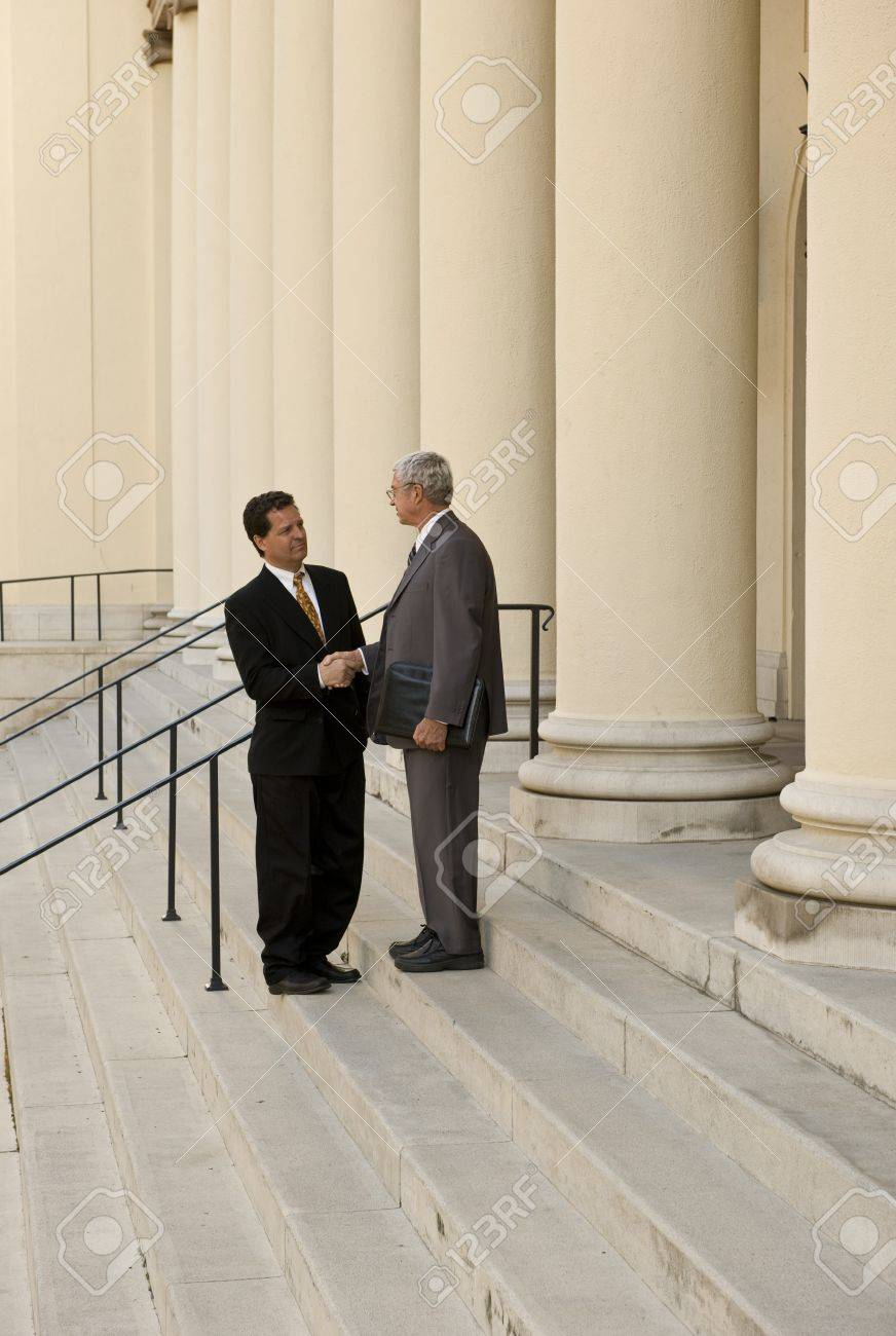 Two men shaking hands on courthouse steps Stock Photo - 9519746