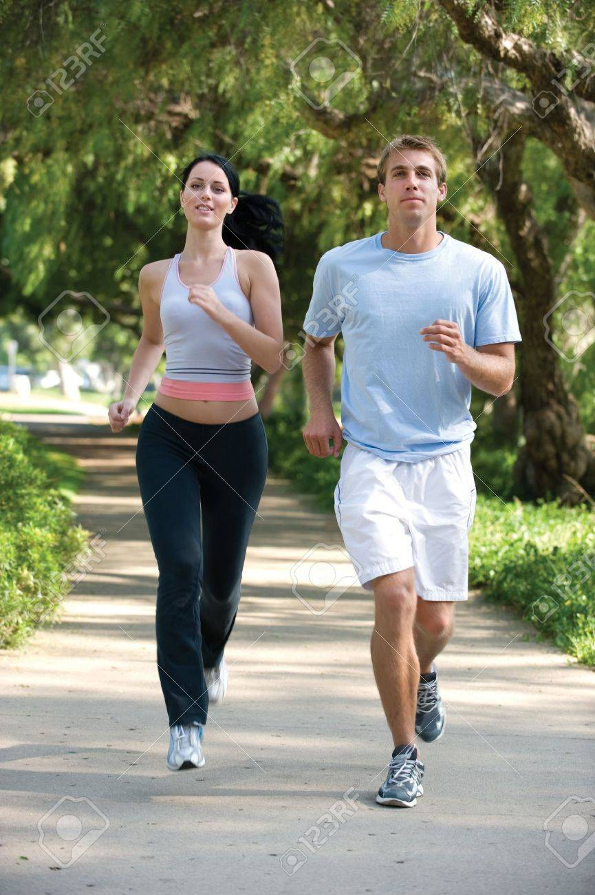 Attractive, young couple jogging in the park Stock Photo - 9519881