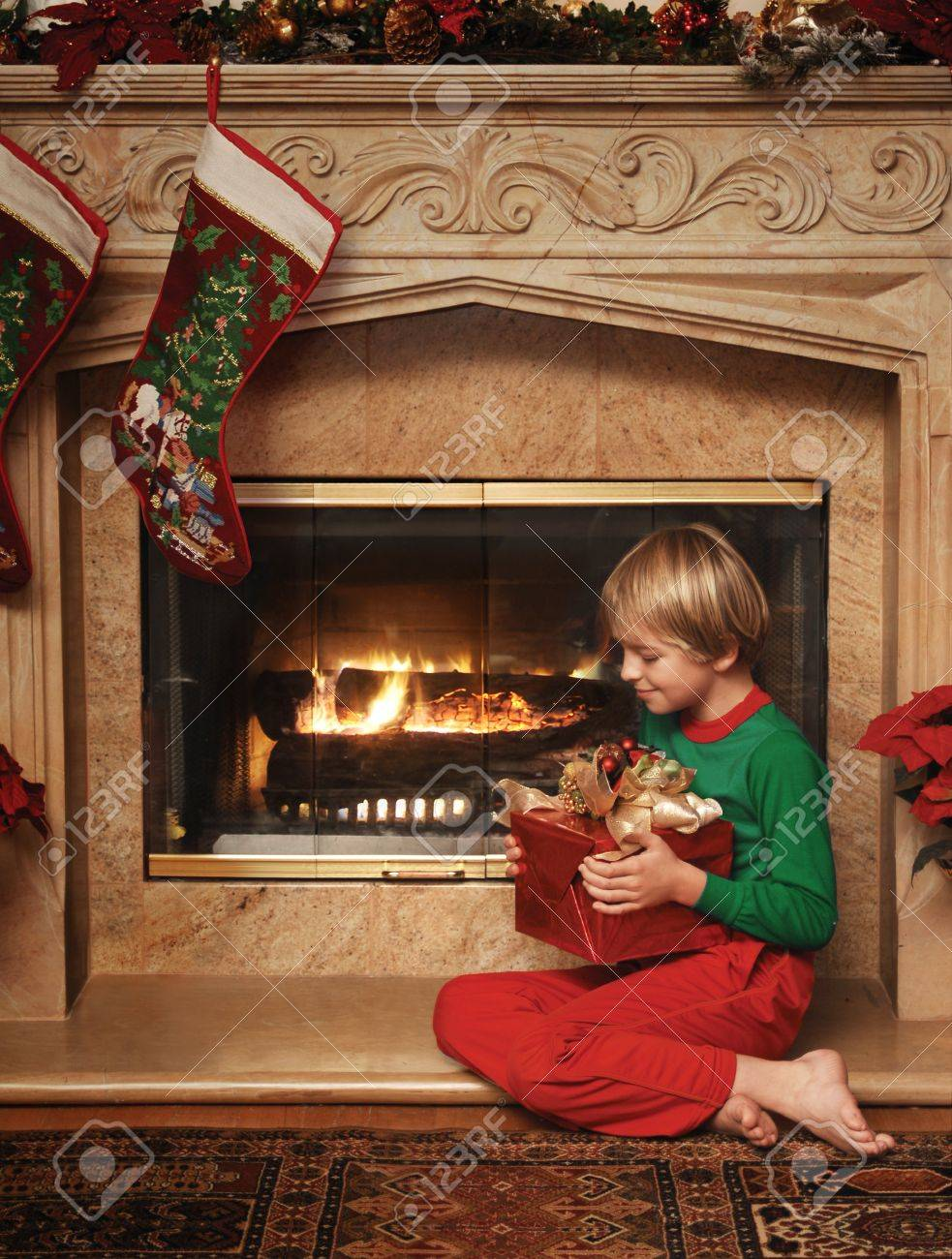 8 Year Old Christmas Gift.8 Year Old Boy Sitting Beside The Fireplace With A Wrapped Christmas