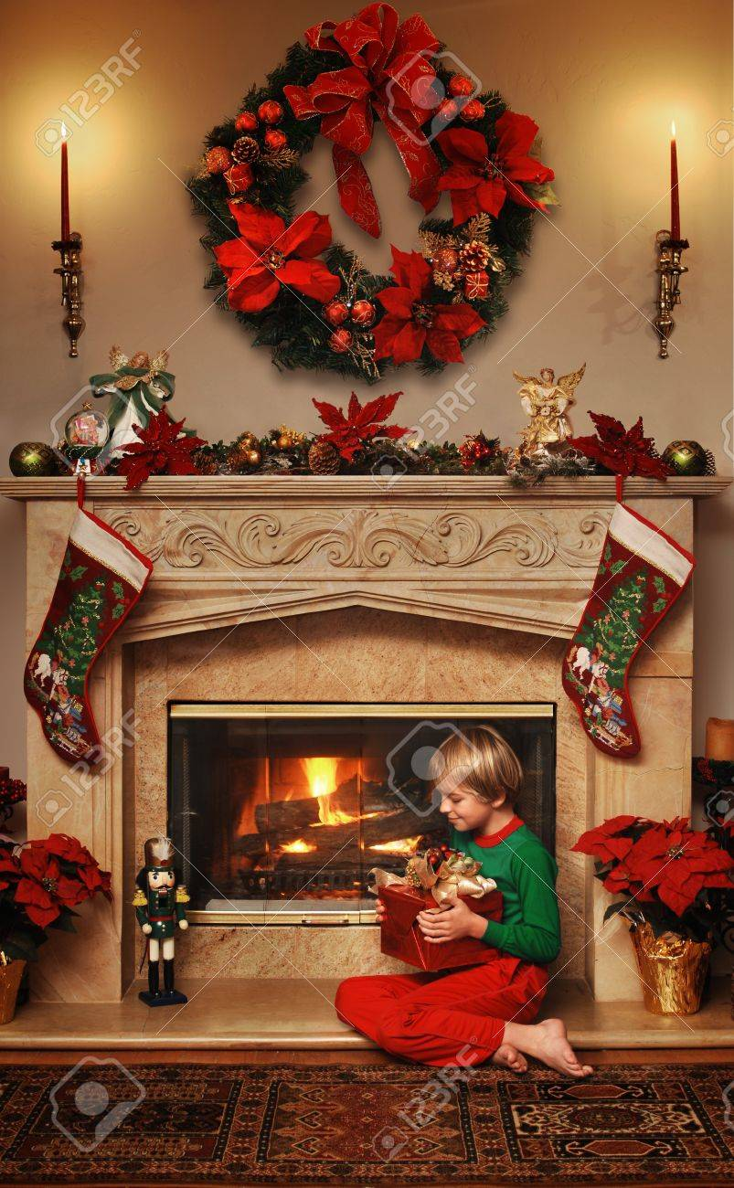8 Year Old Christmas Gift.8 Year Old Boy Sitting Beside The Fire With A Wrapped Christmas