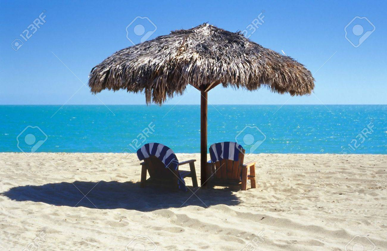 Stock Photo   Tiki Umbrella With Two Adirondack Chairs On The Beach