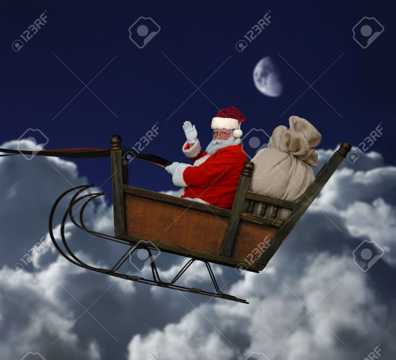 Santa in his sleigh flying throught a nighttime cloudscape Stock Photo - 9519816
