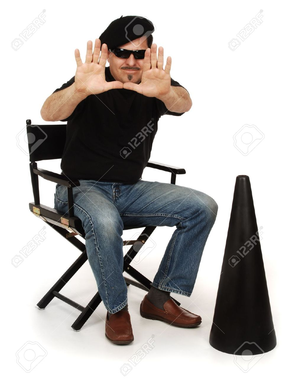 Director wearing berret, and sunglasses sitting in a director's chair with megaphone on white background Stock Photo - 16947230