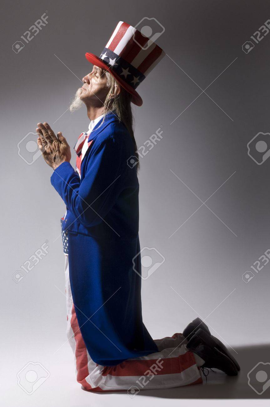 Uncle Sam kneeling in prayer Stock Photo - 9519914