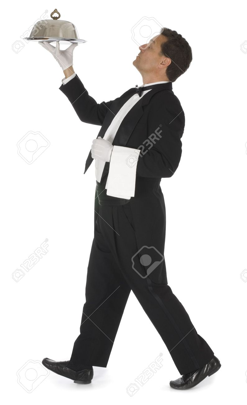 waiter in a black tuxedo carrying a silver tray with a silver