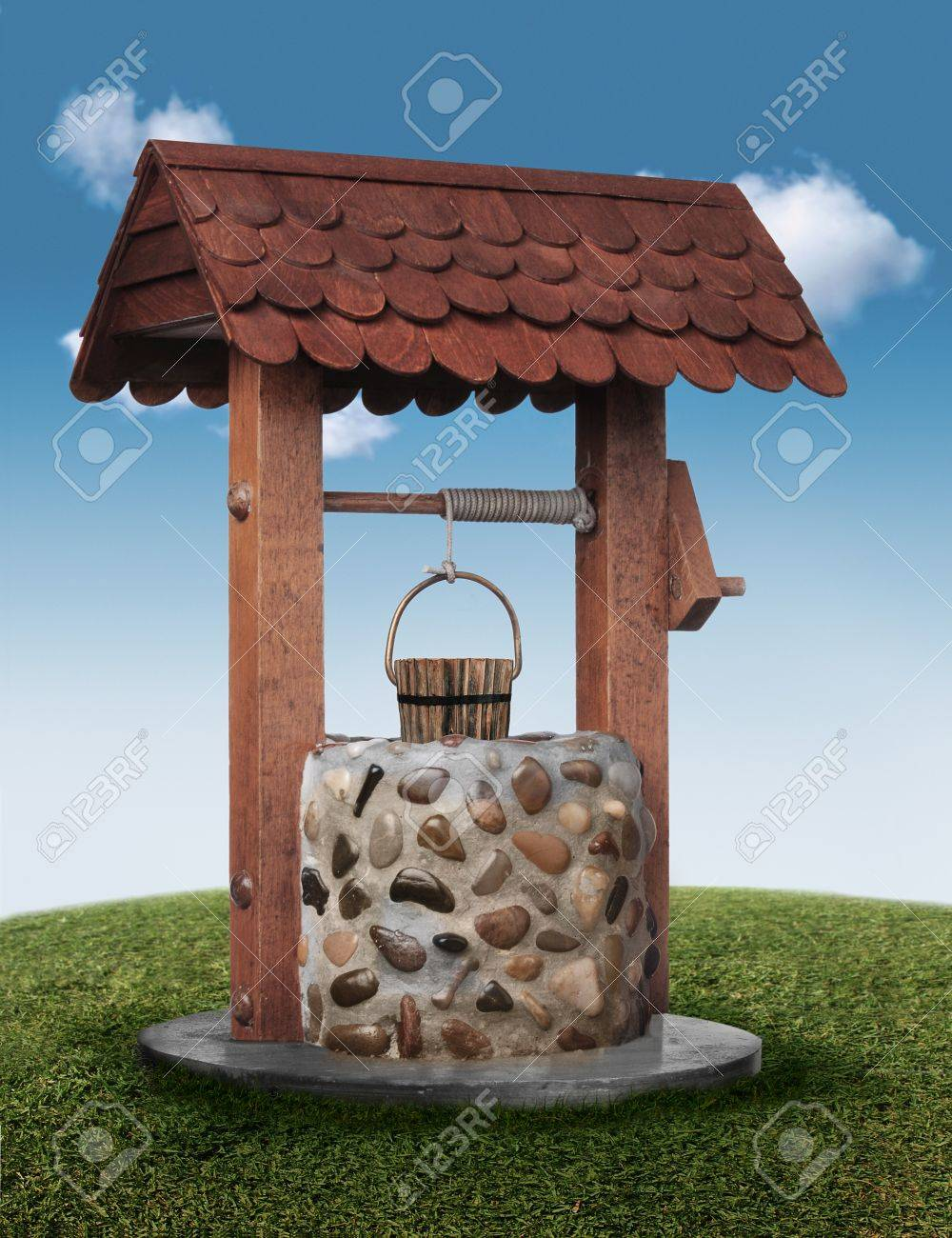 Wishing well on grassy hill with blue sky Stock Photo - 7060240