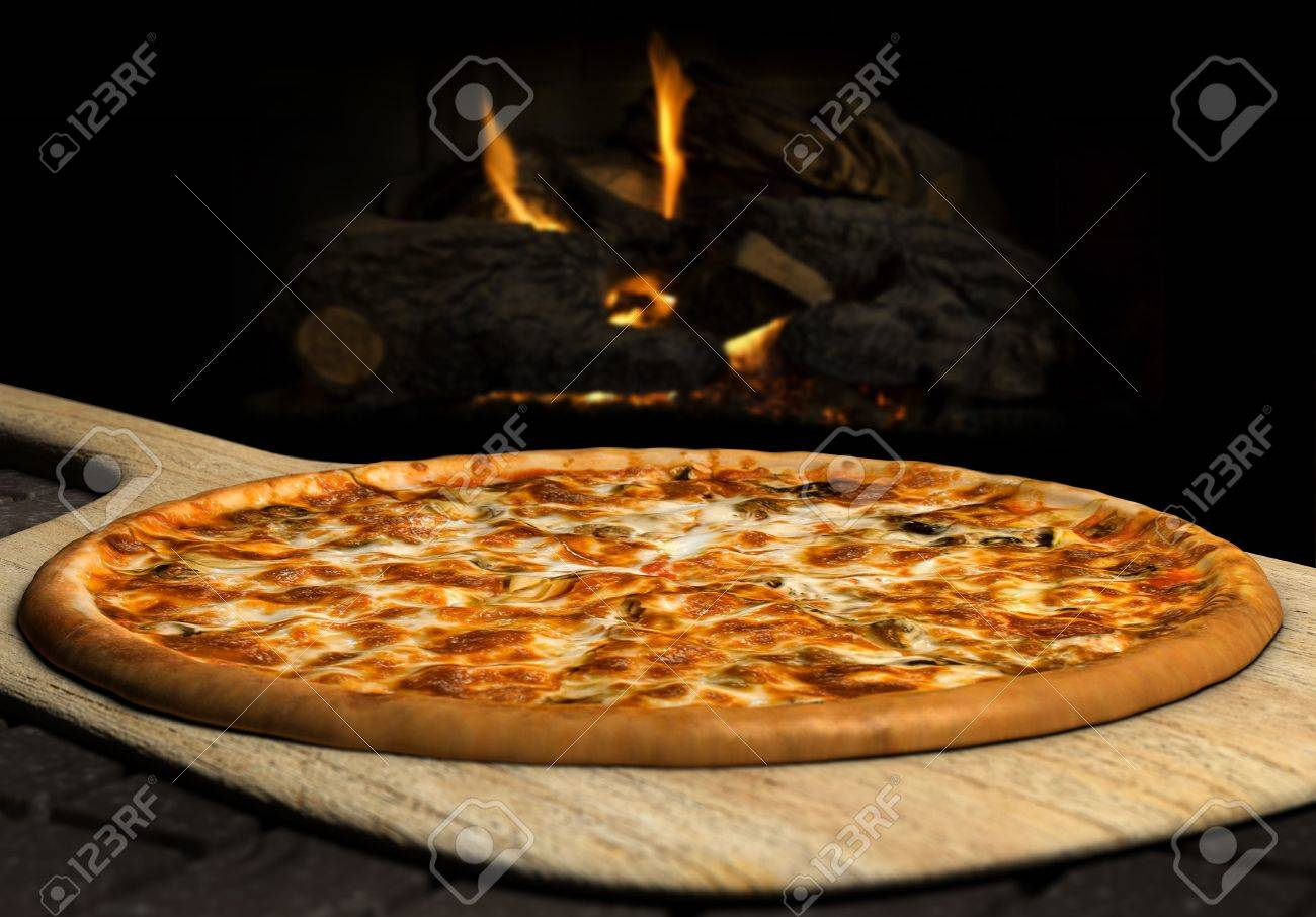 Pizza resting on a pizza peel near an open fire - 7426786