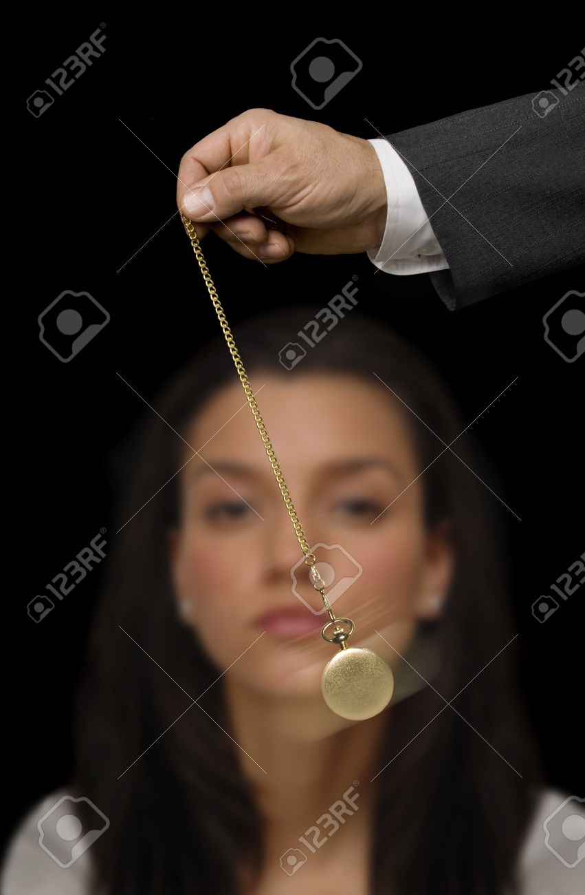 Man's hand holding a pocket watch and swinging it in the fashion of a hypnotist on a black background Stock Photo - 9539324