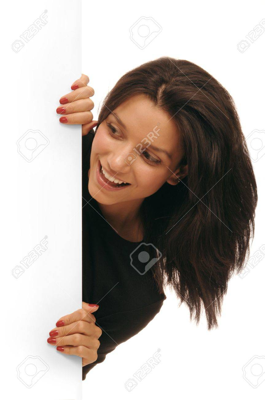 Beautiful young woman peering around from behind a white wall Stock Photo - 9539333