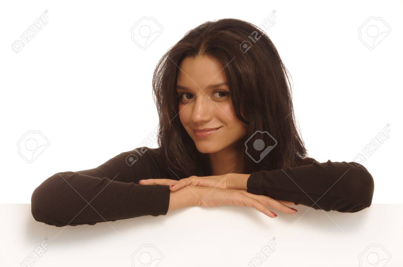 Beautiful young woman behind a white wall resting her arms on the edge looking at the camera Stock Photo - 9539332