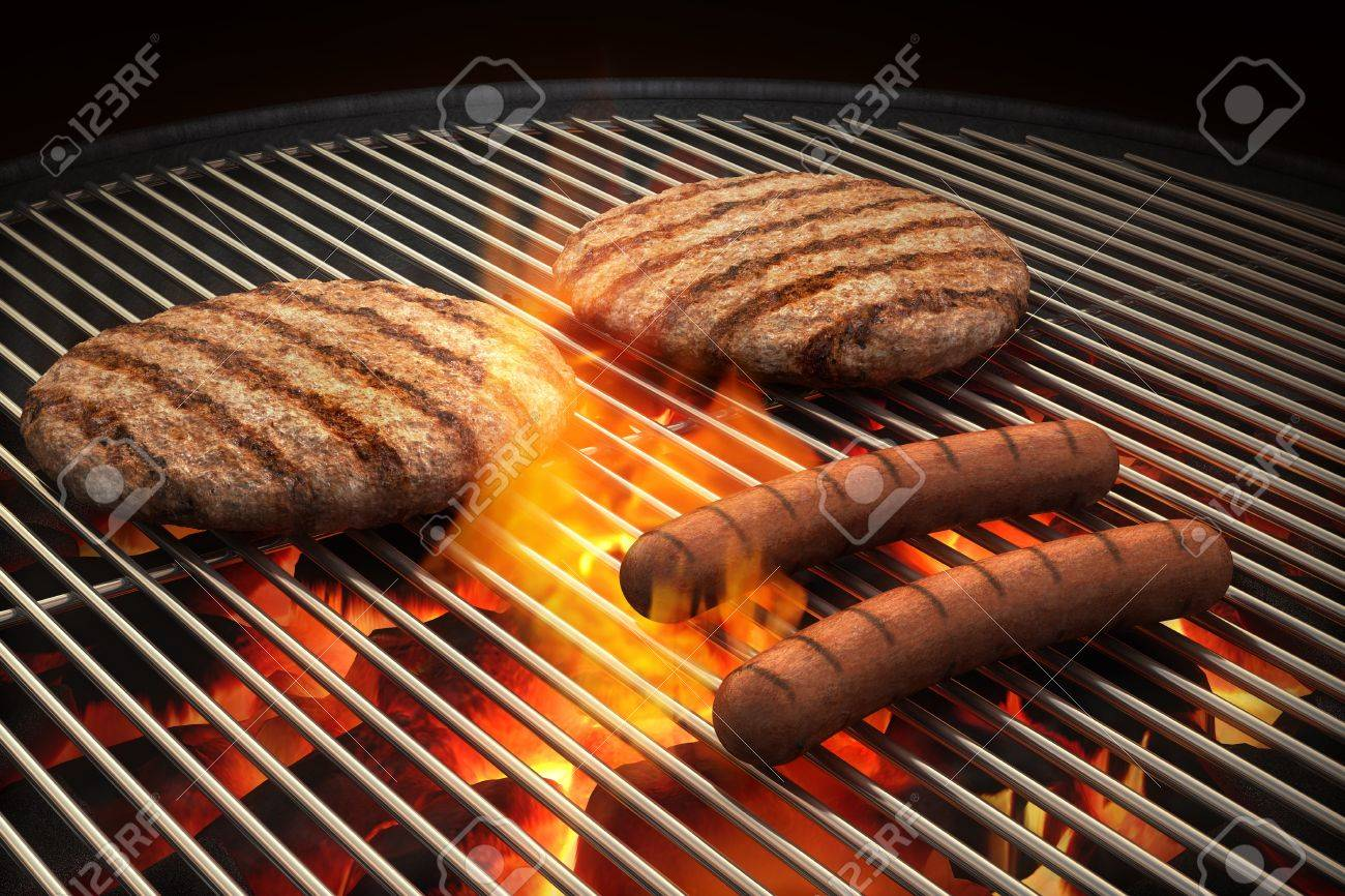 Hamburger patties and hot dogs on the grill under flaming coals Stock Photo - 15440799
