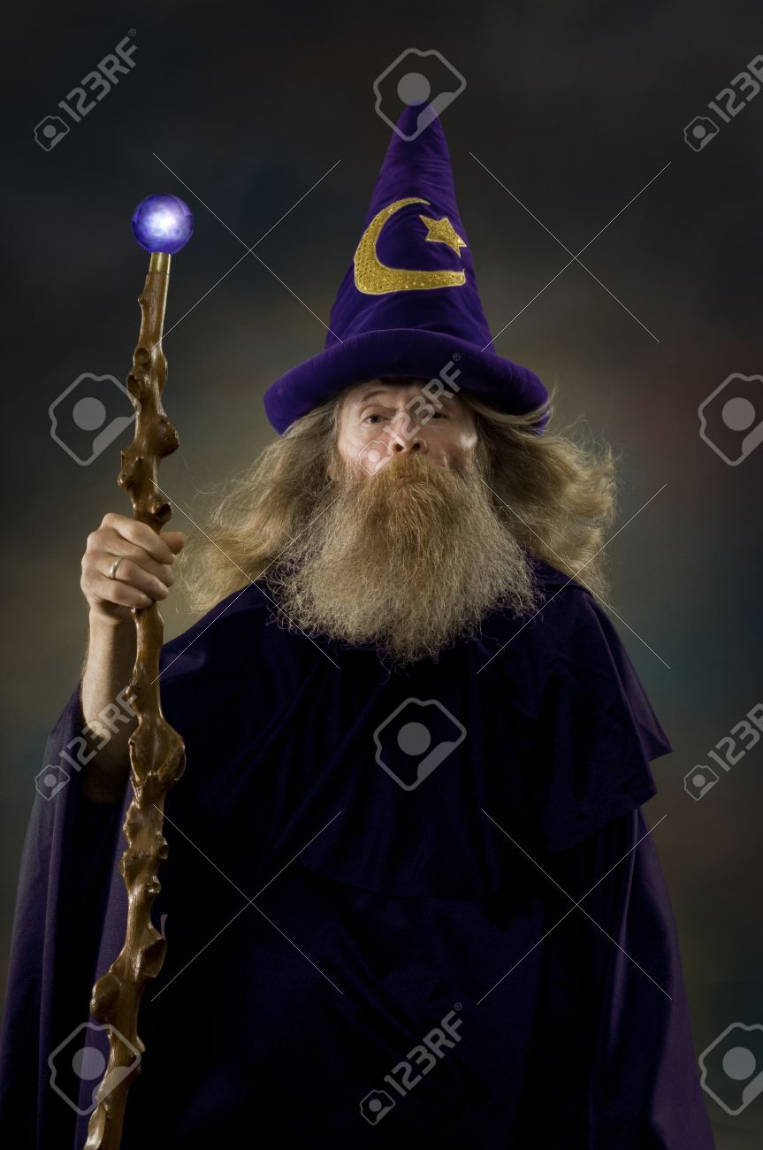 Image Of A Man Dressed As Wizard Holding Glowing Staff Stock Photo