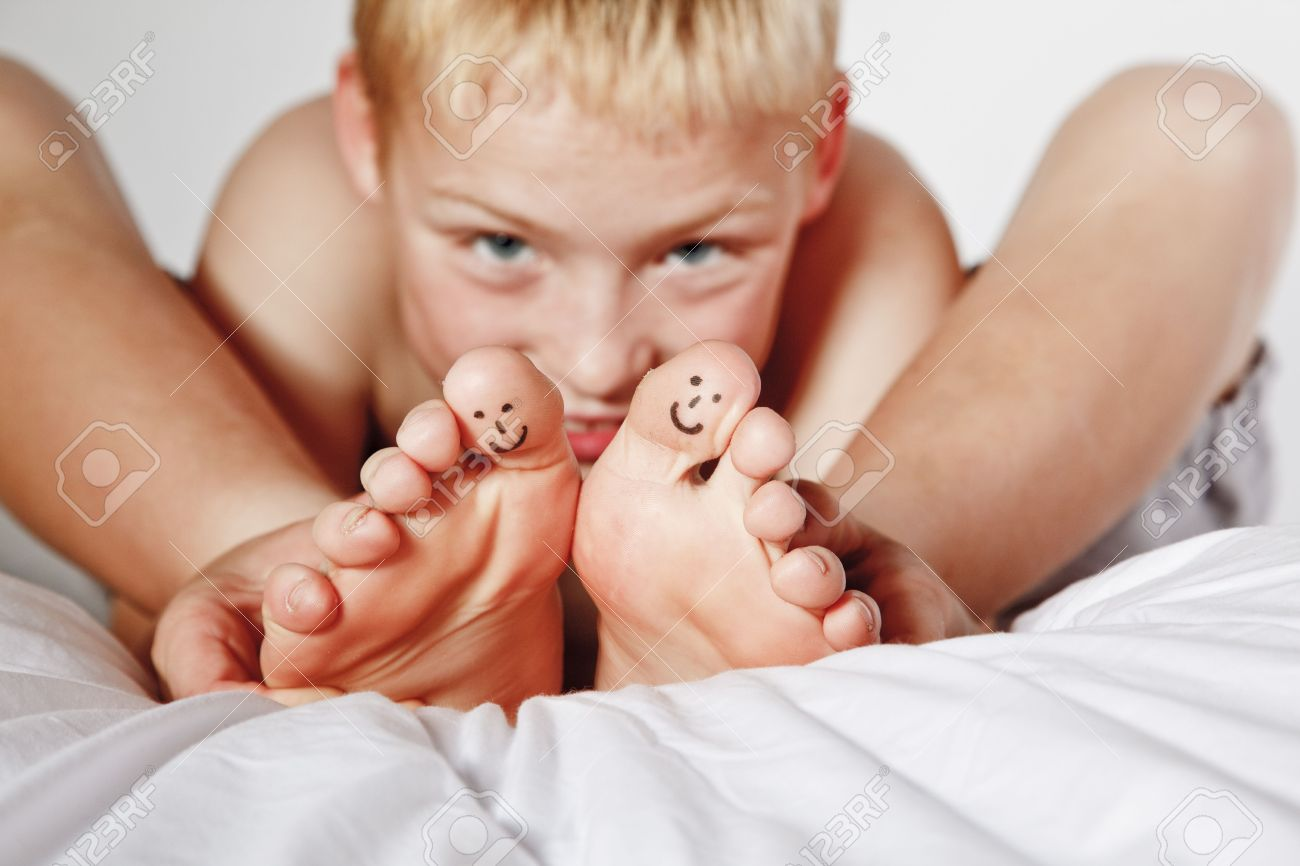 Portrait Of Young Boy In His Bed With Smiley Faces Painted On