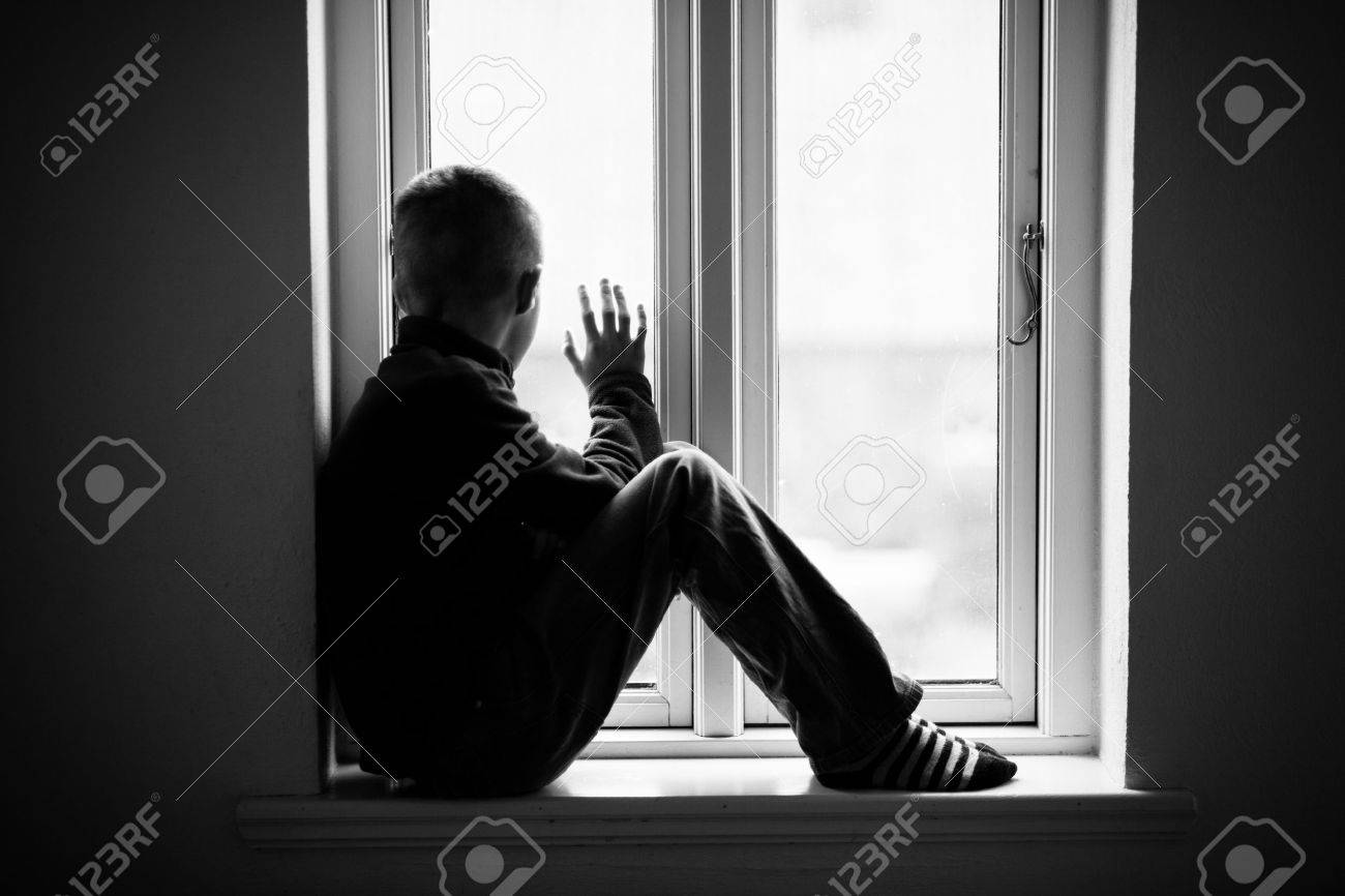 Lonely boy sitting on the windowsill while looking outside view through the glass window in monochrome