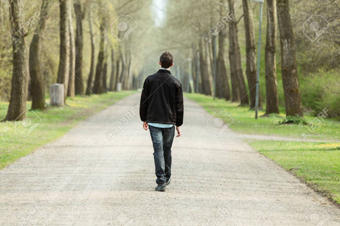 Teenage Boy Walking Away From The Camera Down A Rural Road Lined ...