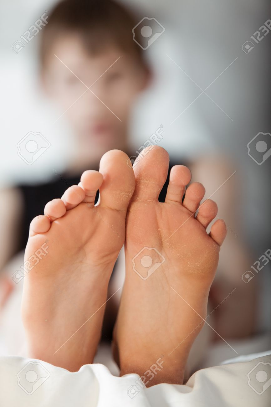 bottom view on pair of feet that belong to an out of focus young boy sitting