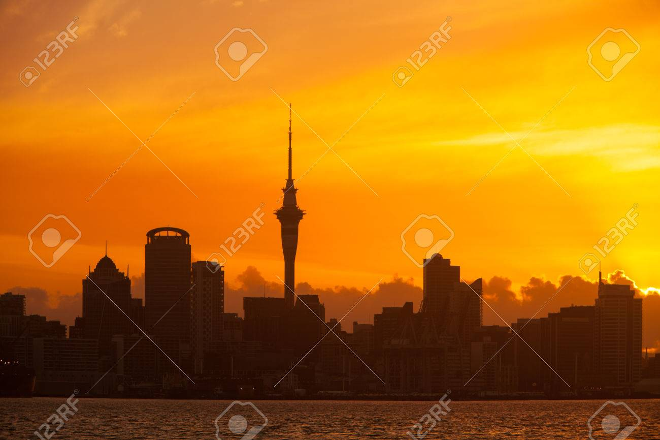 Auckland, New Zealand skyline at sunset with vibrant orange sky and silhouetted buildings. - 36627841