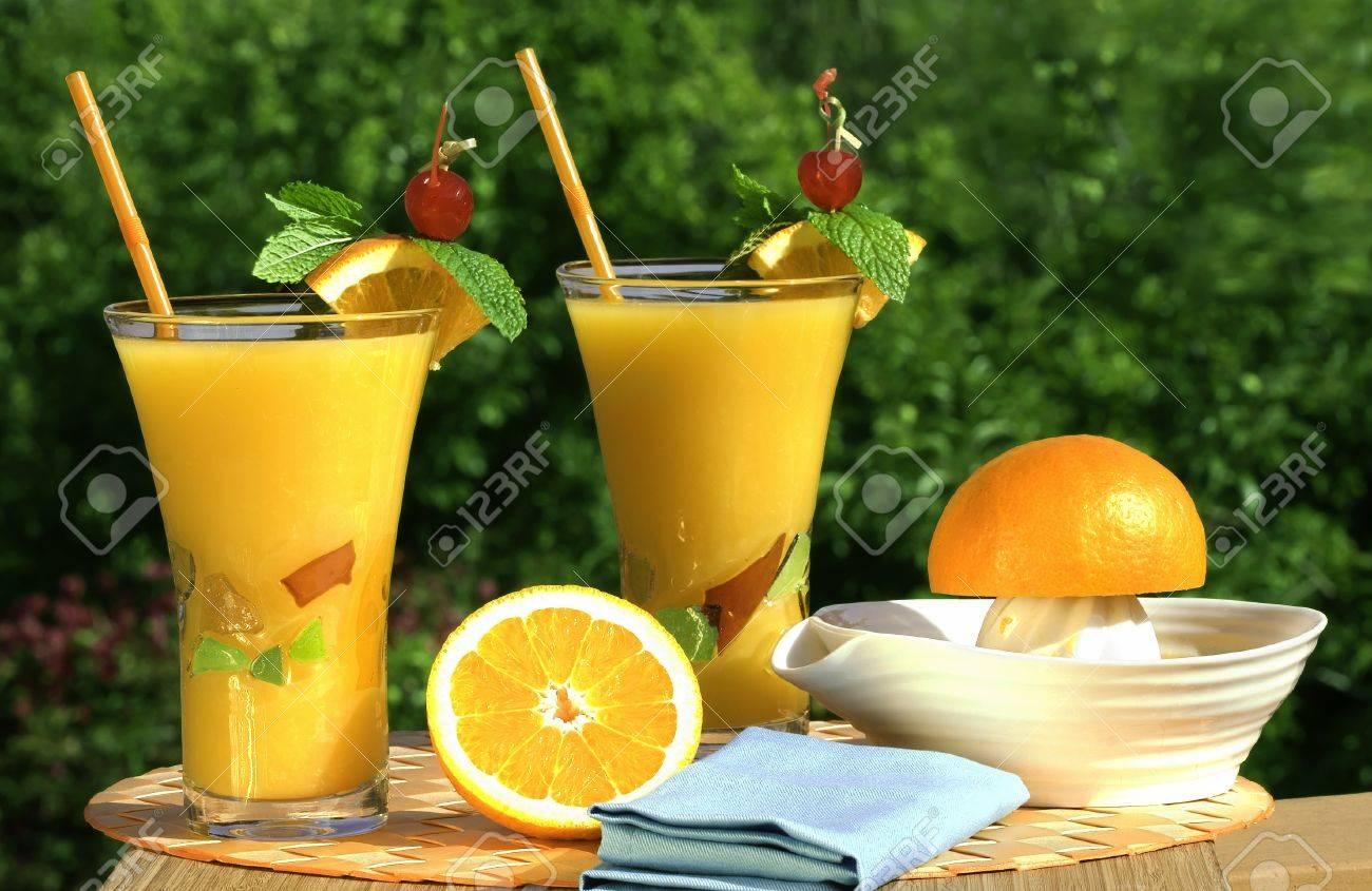 De vidrio es de jugo natural de naranja orgánico exprimidor y las naranjas de fondo natural al aire libre