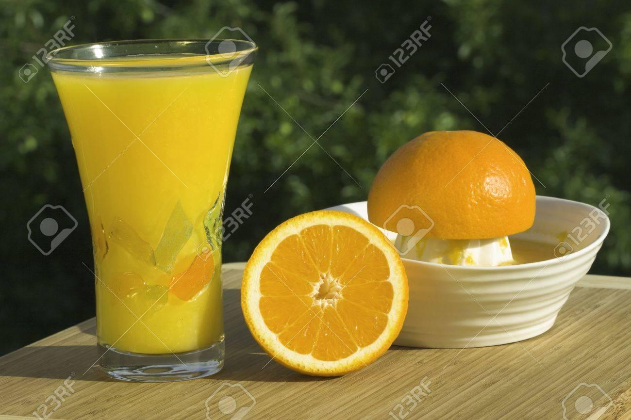 Vaso de fresco jugo de naranja exprimido Orgánica exprimidor y naranjas con fondo natural al aire libre