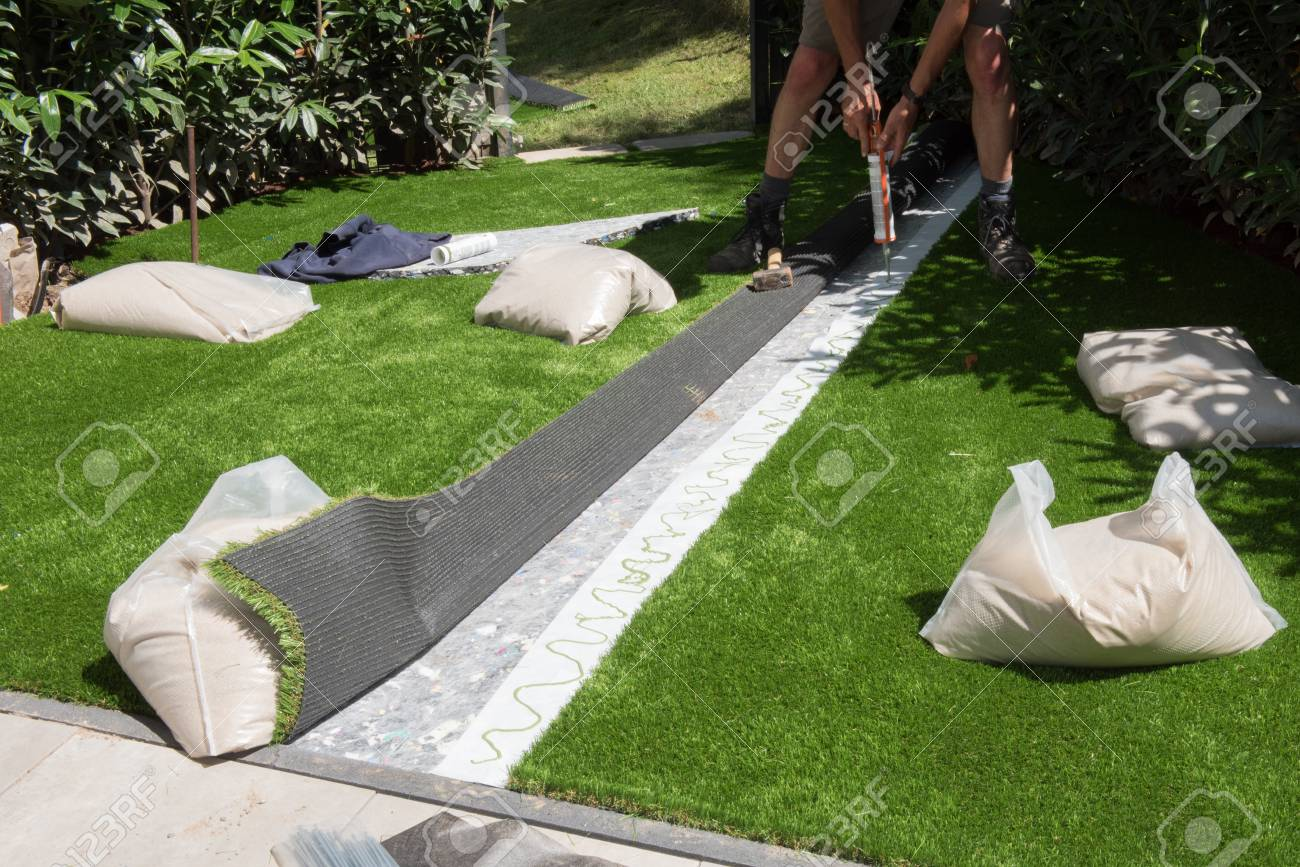 professional gardener is glueing artificial turf to fit - 60102534