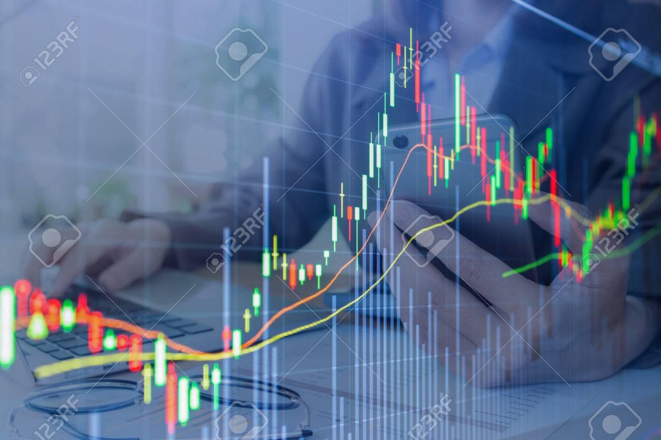 Gráfico de la bolsa de valores. fondo Mujer de negocios la celebración de teléfono inteligente y el uso de equipo portátil para el trabajo en la