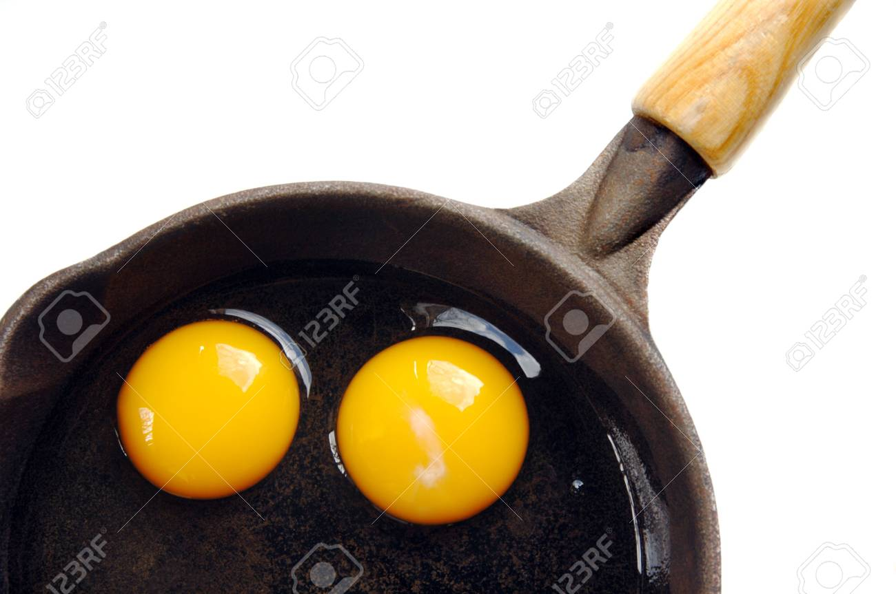 Two eggs in an iron skillet on a white background. Stock Photo - 4740501