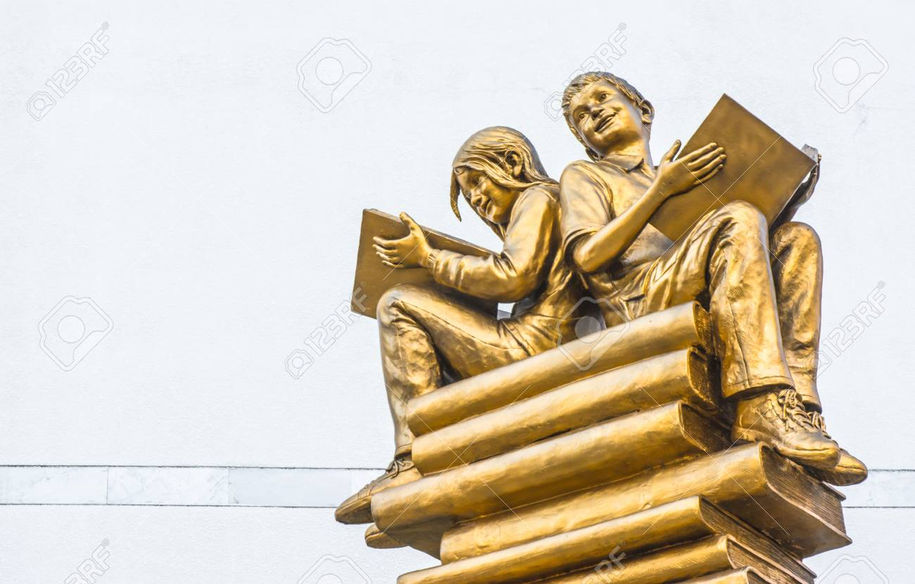 Statue Boy And Girl Sitting On Book At White Concrete Wall In ...