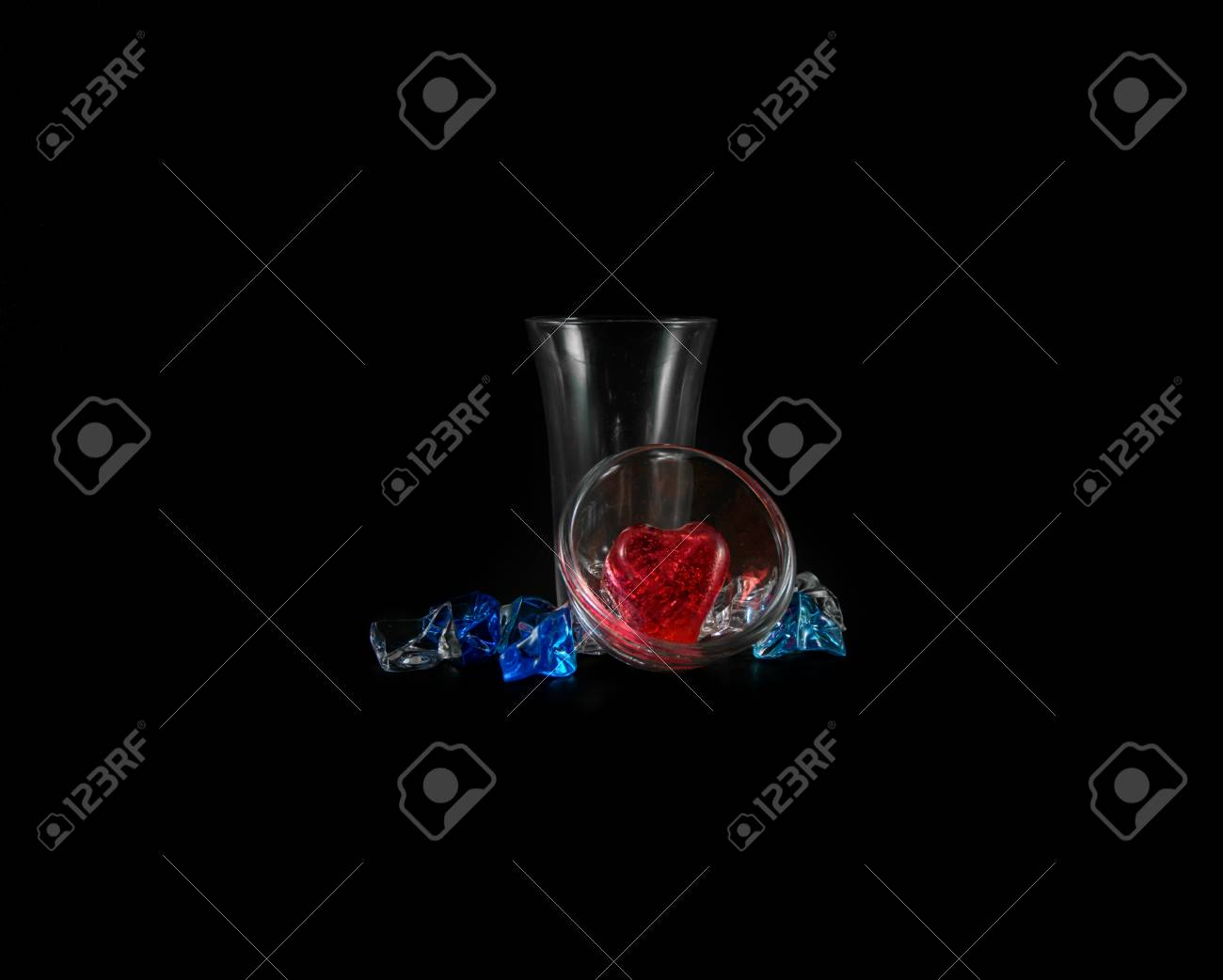 red heart of ice in small glass and ice cube isolated on black background Stock Photo - 21389313