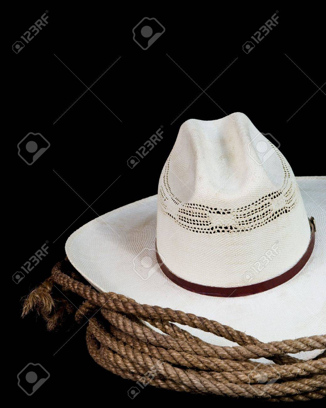 a cowboy hat and lasso on a black background Stock Photo - 9783765