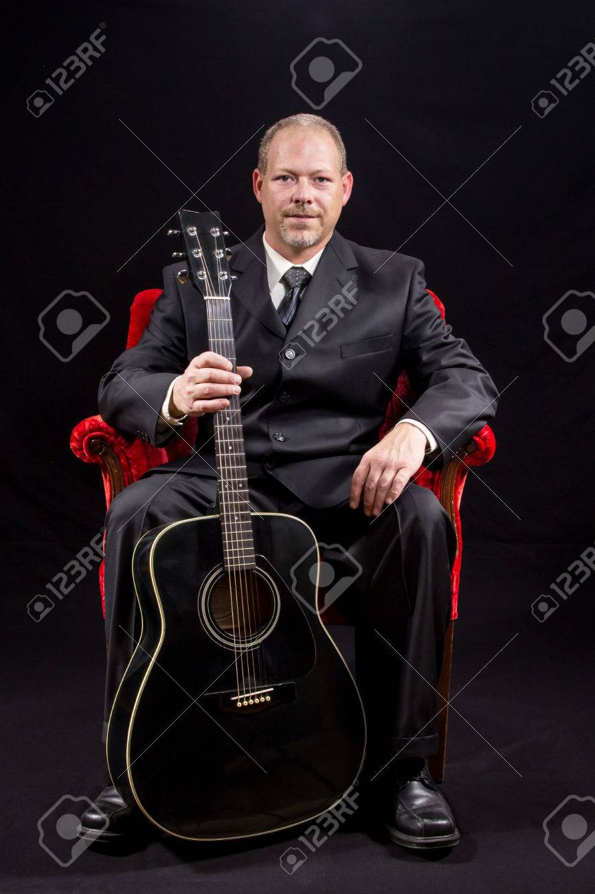 Musician In Business Suit Sitting In Red Velvet Chair Holding