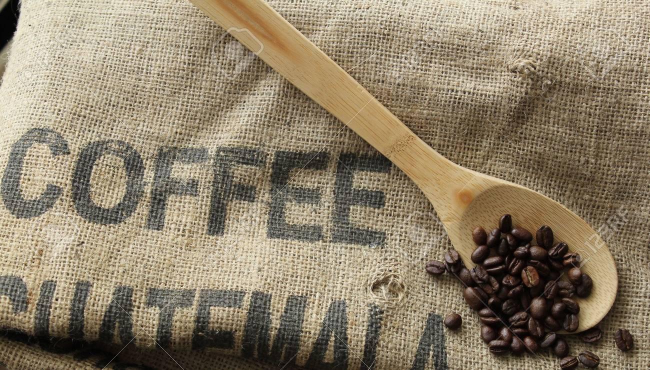 granos de caf en la bolsa de caf cuchara de madera y arpillera foto de archivo