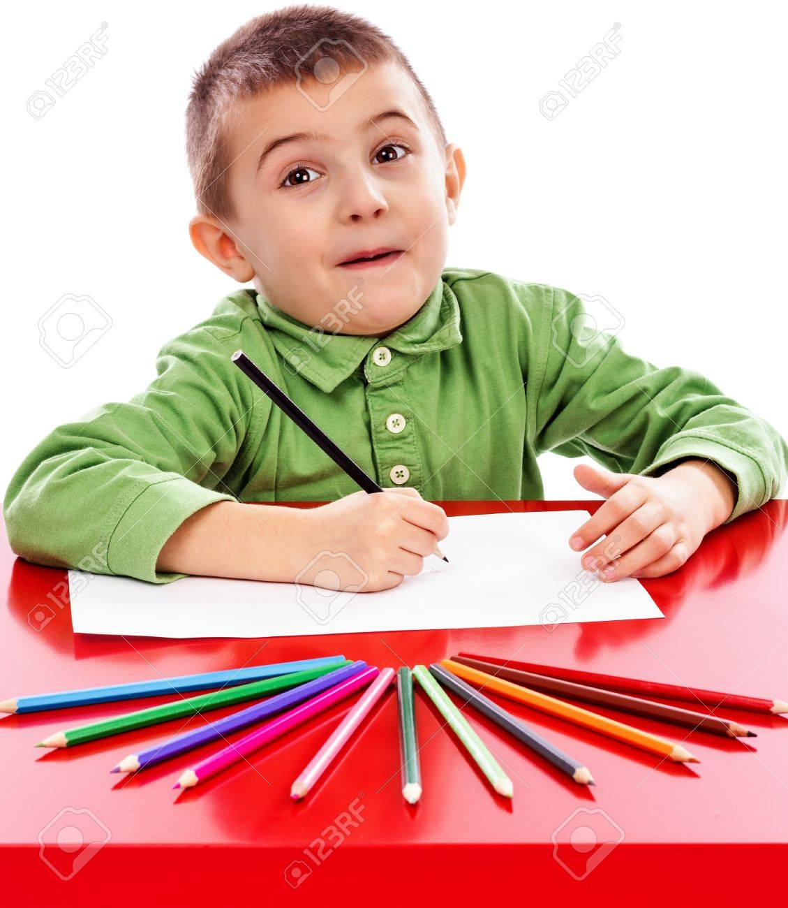 Happy Little Boy At The Table Drawing With Crayons Isolated On White Stock Photo